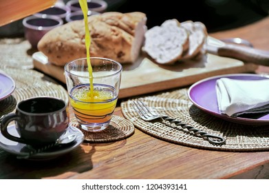 Orange juice is pouring into the glass during breakfast on wooden table in the morning.coffee cup