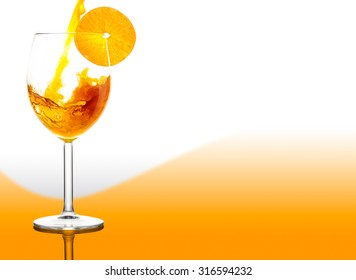 Orange juice pouring in wine glass with summer gradient background