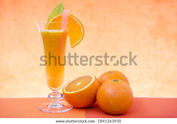 Orange juice and slice on the glass, oranges on the table