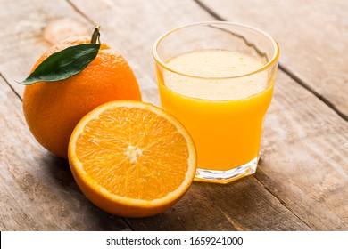 Orange juice and orange slices on wooden table