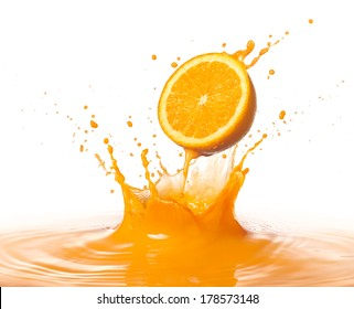 orange juice splashing with its fruit against white background