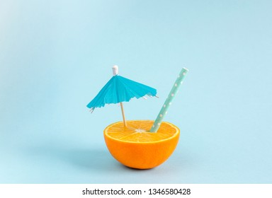 Orange juice with straw and umbrella. Orange cut in half on pastel blue background. Minimal summer concept. Flat lay