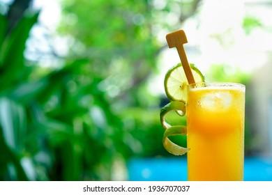Orange juice view over swimming pool