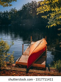 orange kayak on dry dock on a lake in Maine, New England, during season of Fall.