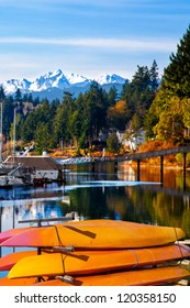 Orange kayaks by the water with a background of snow covered Olympic Mountains in Washington State. Location: Port Ludlow