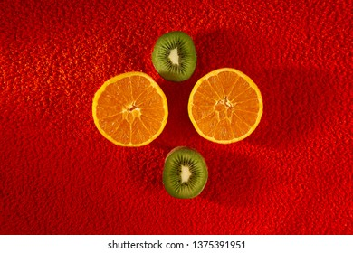 orange and kiwi cut in half on red cloth with thread texture
