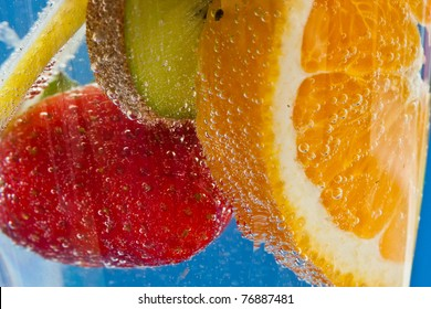 Orange, kiwifruit, lemon and strawberry cocktail - in soda water - against an ultramarine blue background