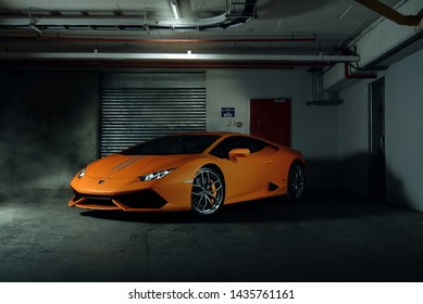 Orange Lamborghini Huracan full front, shot against industrial background.