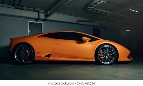 Orange Lamborghini Huracan side profile shot, industrial background.