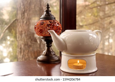 orange lamp and a white teapot with a burning candle under it on the table