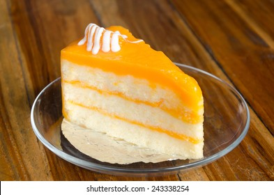 Orange layer cake on Wooden table.