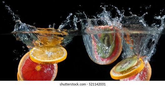 Orange, lemon, grapefruit and kiwi splashing into water on a black background