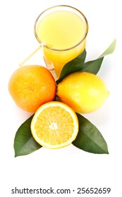 Orange and lemon with green leaves and glass of juice on a white background