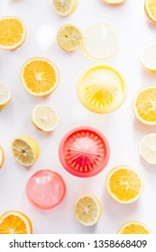 Orange and lemon juice maker, fresh summer juice, cut lemon and orange fruit with red and yellow juice container and squeezer,top view, on a white board with strong backlight