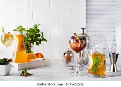 Orange lemonade in the decanter on a wooden tray, cocktails glasses and ginger and Cocktail shaker with a place for your subject and text