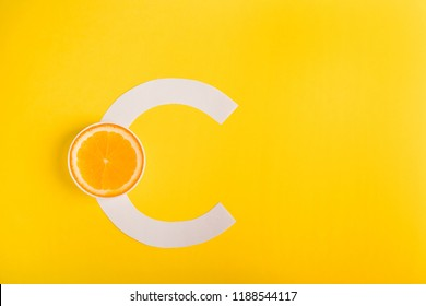 Orange and letter C on a yellow background. The concept of Vitamin S. Autumn protection against colds, antioxidant