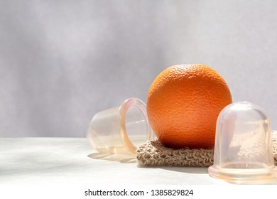 The orange lies on a mesh washcloth made from natural fibers, and next to it are vacuum banks.