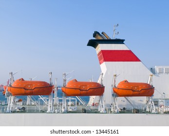 Orange life boats on a cruiseship docked at port waiting for passengers to board