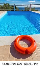 Orange life buoy lies at blue greek swimming pool near coast