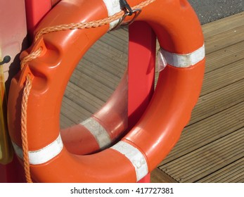 Orange life buoy on wooden pier in the harbor