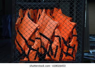 Orange Life Jacket, Life Jacket In Storage Room, Wire Mesh Inside The Room.