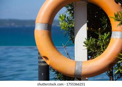 Orange life ring on the blue sea background