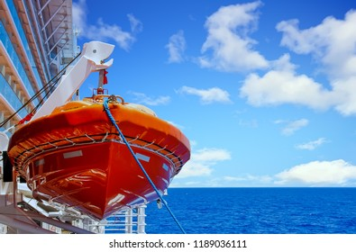 Orange Lifeboat Hanging From Harness Over Deep Blue Sea