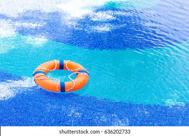 Orange lifebuoy float in pool with copy space