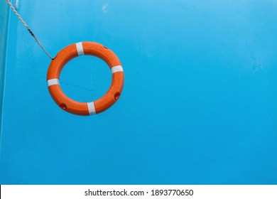 Orange lifebuoy floats on blue water in the sea. Help and protection of life. Summer vacation