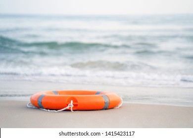 Orange lifebuoy lies on the shore on a sunny day against the background of the sea. Red lifebuoy on the background of the ocean.  Life ring on the sea sand.