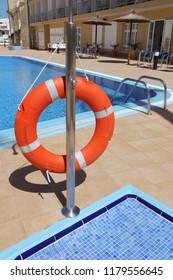 Orange lifebuoy or lifebelt hanging next to the swimming pool of a hotel.