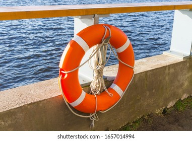 Orange lifebuoy and old rope hanging by the river.