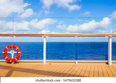 Orange lifebuoy on a deck of cruise ship with ocean on background with copy space