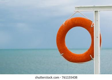 orange lifebuoy on the sea coast on cloudy day