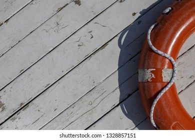 orange lifebuoy on wooden background. Life buoy hanging on wooden wall for emergency response when people sinking to water almost place near pool and beach. Orange lifebuoy on wooden floor in port.