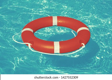 Orange lifebuoy pool ring float on blue water. Life ring floating on top of sunny blue water. Life ring in swimming pool. Toning