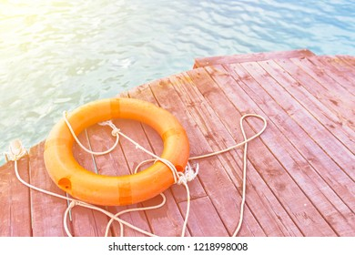 Orange lifebuoy with rope on a wooden pier near sea. Lifebuoy, safety equipment, at the pier. Important safety equipment for lifesaving in river, lake and beach.