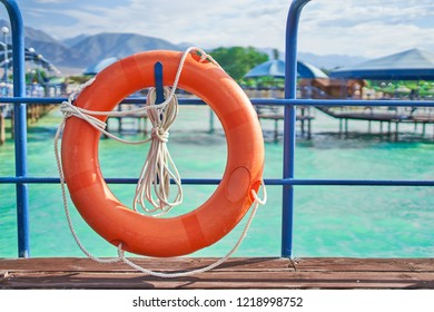 Orange lifebuoy with rope on a wooden pier near sea. Closeup of lifebuoy on dock. Rescue equipment for emergency on water. Dock sea background.
