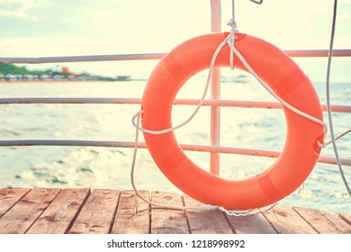 Orange lifebuoy with rope on a wooden pier near sea. Lifebuoy at the pier. Save lifebuoy and blue water.