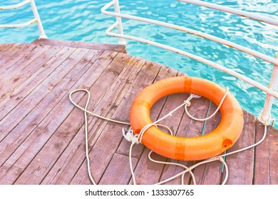 Orange lifebuoy with rope on a wooden pier near sea. Lifebuoy with rope on a wooden pier near sea.