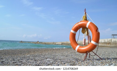 orange lifebuoy in the sandy beach in front of the mediterranean sea, lifebelt with rope on the beach. Lifebuoy on the beach