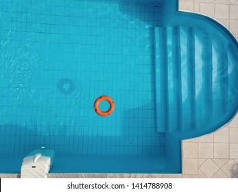 Orange lifebuoy in a swimming pool in summer