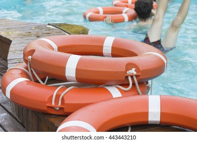 Orange lifebuoy in the swimming pool with turquoise water
