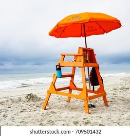 An orange lifeguard stand and umbrella on the beach