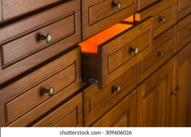 orange light from drawer, concept of secret,   storage of valuable objects