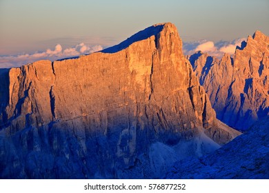 Orange light illuminates steep cliffs at sunset, Dolomite Alps, Italy
