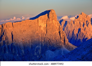 Orange light illuminates steep walls at sunset, Dolomite Alps, Italy