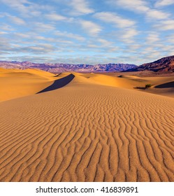 Orange light in the morning over sand dunes. Deep shadows in the hollows. Mesquite Flat Sand Dones in Death Valley