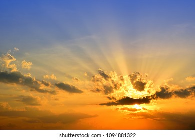 Orange light with sun rays and dark clouds on sky before sunset in the evening.
