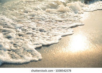 The orange light wave of the ocean on a sandy beach sunset in the background.